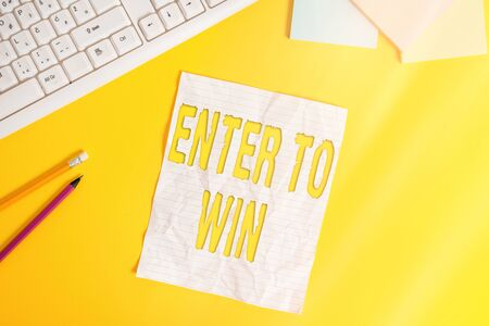 Word writing text Enter To Win. Business photo showcasing exchanging something value for prize chance winning prize Copy space on notebook above yellow background with pc keyboard on the table
