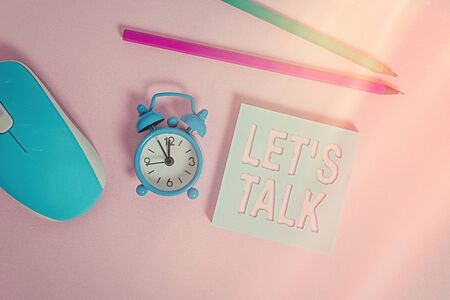 Text sign showing Let S Talk. Business photo showcasing they are suggesting beginning conversation on specific topic Alarm clock wakeup blank notepad mouse markers colored background Stock Photo