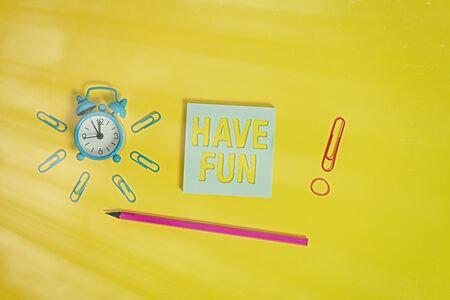 Writing note showing Have Fun. Business concept for wish somebody good and enjoyable time when they do something Alarm clock wakeup clips rubber band pencil notepad colored background Stock fotó