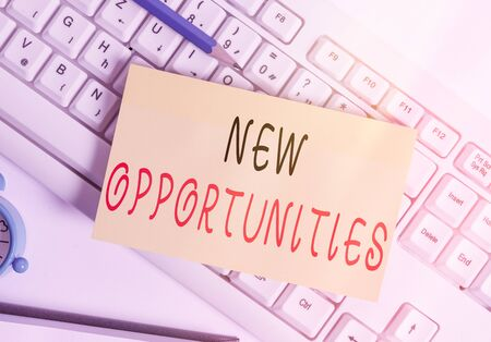 Writing note showing New Opportunities. Business concept for exchange views condition favorable for attainment goal White pc keyboard note paper and paper clips above white background