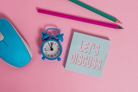 Text sign showing Let S Discuss. Business photo showcasing asking someone to talk about something with an individual or showing Alarm clock wakeup blank notepad mouse markers colored background