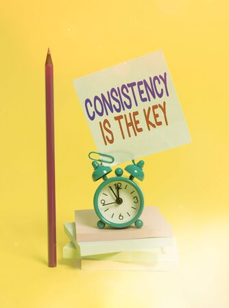 Conceptual hand writing showing Consistency Is The Key. Concept meaning by Breaking Bad Habits and Forming Good Ones Alarm clock sticky note notepads pencil colored background