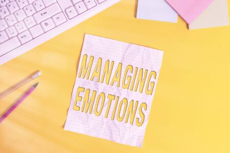Word writing text Managing Emotions. Business photo showcasing ability be open to feelings and modulate them in oneself Copy space on notebook above yellow background with pc keyboard on the table Archivio Fotografico