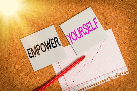 Text sign showing Empower Yourself. Business photo text taking control of our life setting goals and making choices Desk notebook paper office cardboard paperboard study supplies table chart
