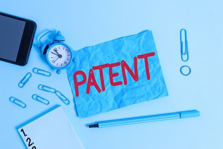 Conceptual hand writing showing Patent. Concept meaning government authority or licence conferring a right or title Alarm clock notepad smartphone band marker colored background