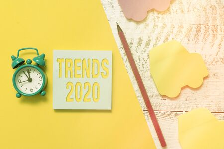 Text sign showing Trends 2020. Business photo showcasing general direction in which something is developing or changing Notepad car sticky notes pen paper sheet alarm clock wooden background