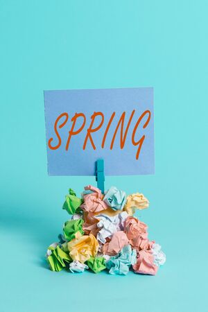 Handwriting text Spring. Conceptual photo the season after winter in which vegetation begins to appear Reminder pile colored crumpled paper clothespin reminder blue background