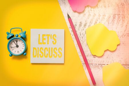 Text sign showing Let S Discuss. Business photo showcasing asking someone to talk about something with an individual or showing Notepad car sticky notes pen paper sheet alarm clock wooden background