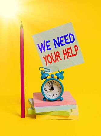 Conceptual hand writing showing We Need Your Help. Concept meaning asking someone to stand with you against difficulty Alarm clock sticky note notepads pencil colored background Banque d'images
