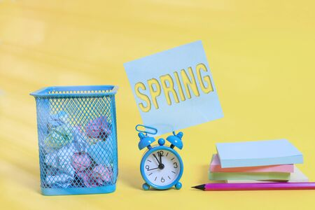 Writing note showing Spring. Business concept for the season after winter in which vegetation begins to appear Alarm clock pencil note paper balls container pads colored background