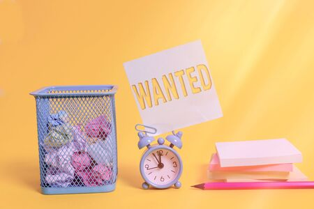 Writing note showing Wanted. Business concept for Desire something Wish want Hoping for Somebody being searched Alarm clock pencil note paper balls container pads colored background