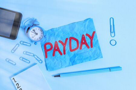Conceptual hand writing showing Payday. Concept meaning a day on which someone is paid or expects to be paid their wages Alarm clock notepad smartphone band marker colored background