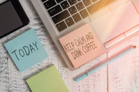 Word writing Keep Calm And Drink Coffee in office with laptop, marker, pen, stationery, coffee. Business concept for encourage an individual to enjoy caffeine drink and relax Workshop white background with space