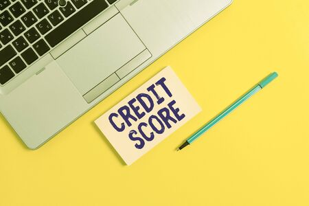 Handwriting text writing Credit Score. Conceptual photo Represent the creditworthiness of an individual Lenders rating Trendy silver open laptop square sticky notepad marker colored background
