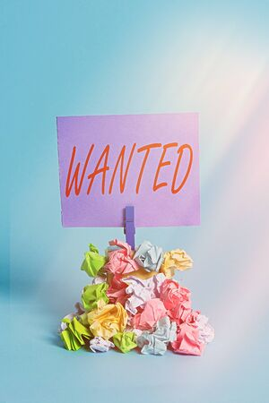 Handwriting text Wanted. Conceptual photo Desire something Wish want Hoping for Somebody being searched Reminder pile colored crumpled paper clothespin reminder blue background