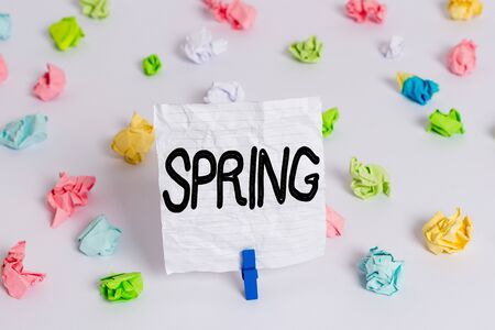 Writing note showing Spring. Business concept for the season after winter in which vegetation begins to appear Colored crumpled paper empty reminder white floor clothespin