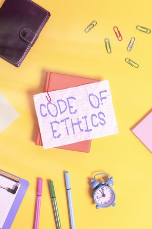 Writing note showing Code Of Ethics. Business concept for basic guide for professional conduct and imposes duties Flat lay above empty paper with pencils and paper clips