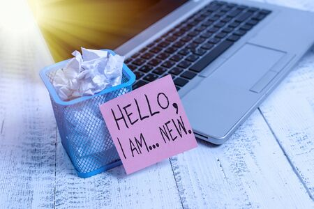 Text sign showing Hello I Am New. Business photo showcasing used greeting or begin telephone conversation Metallic laptop sticky note pad waste basket crushed paper vintage table