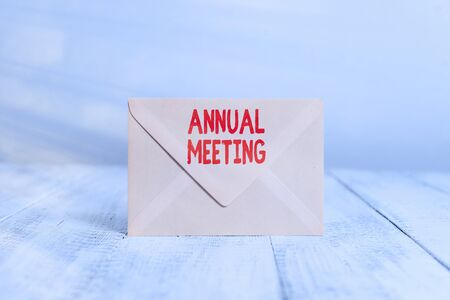 Handwriting text writing Annual Meeting. Conceptual photo yearly meeting of the general membership of an organization Closed standing rectangular colored envelope old wooden vintage background