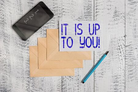 Conceptual hand writing showing It Is Up To You. Concept meaning Used to tell an individual that they are the one to decide Envelopes marker ruled paper smartphone wooden background
