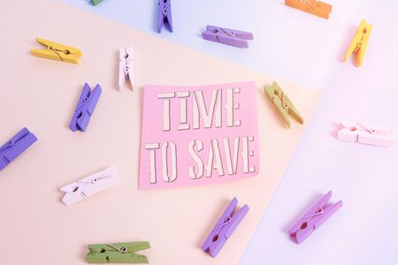 Writing note showing Time To Save. Business concept for to do something more efficiently that less time is required Colored clothespin paper reminder with yellow blue background