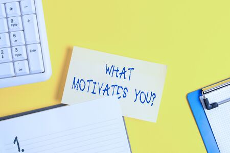 Writing note showing What Motivates Youquestion. Business concept for know reasons why you want to wake up each morning Empty orange paper with copy space on the yellow table