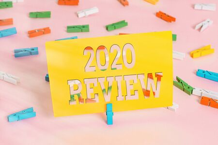 Text sign showing 2020 Review. Business photo text New trends and prospects in tourism or services for 2020 Colored clothespin papers empty reminder pink floor background office pin