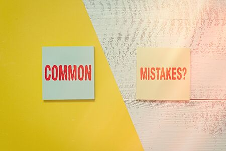 Text sign showing Common Mistakes Question. Business photo showcasing repeat act or judgement misguided making something wrong Two multicolor blank notepads colored paper sheet retro wooden background Фото со стока