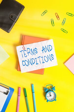 Writing note showing Terms And Conditions. Business concept for rules that apply to fulfilling a particular contract Flat lay above empty paper with pencils and paper clips Reklamní fotografie