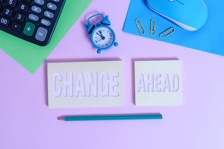 Handwriting text Change Ahead. Conceptual photo to replace with or exchange for another Become different Wire mouse clock calculator notepads marker sheets clips color background