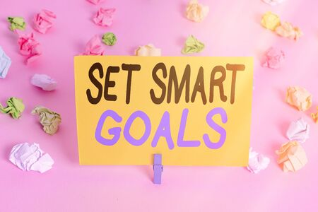 Text sign showing Set Smart Goals. Business photo text giving criteria to guide in the setting of objectives Colored crumpled papers empty reminder pink floor background clothespin