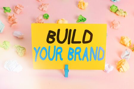 Text sign showing Build Your Brand. Business photo text enhancing brand equity using advertising campaigns Colored crumpled papers empty reminder pink floor background clothespin