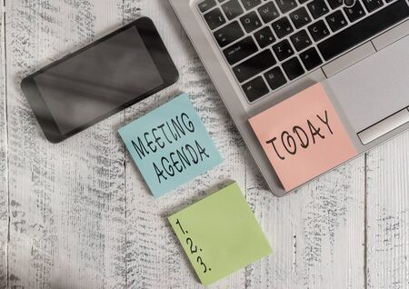 Word writing text Meeting Agenda. Business photo showcasing items that participants hope to accomplish at a meeting Metallic slim laptop sticky note pads smartphone lying old wooden table Фото со стока