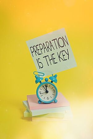 Handwriting text Preparation Is The Key. Conceptual photo it reduces errors and shortens the activities Metal alarm clock blank sticky note stacked notepads colored background