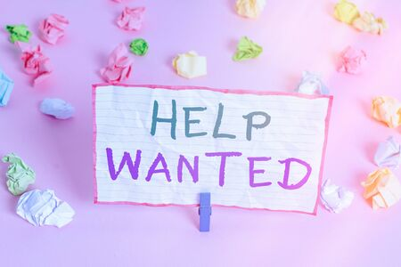 Text sign showing Help Wanted. Business photo text An ad in the paper an employer places to find a new employee Colored crumpled papers empty reminder pink floor background clothespin Imagens