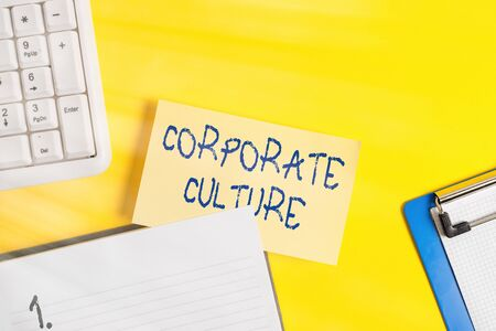 Writing note showing Corporate Culture. Business concept for pervasive values and attitudes that characterize a company Empty orange paper with copy space on the yellow table Фото со стока