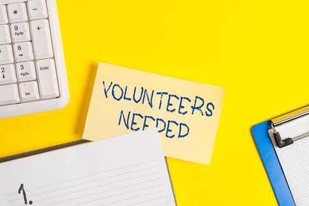 Writing note showing Volunteers Needed. Business concept for need work or help for organization without being paid Empty orange paper with copy space on the yellow table