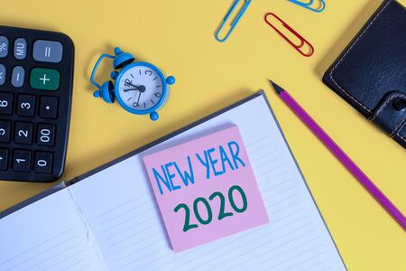 Text sign showing New Year 2020. Business photo showcasing Greeting Celebrating Holiday Fresh Start Best wishes Notebook wallet calculator clips pencil note alarm clock color background