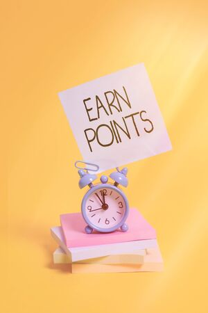 Handwriting text Earn Points. Conceptual photo getting praise or approval for something you have done Metal alarm clock blank sticky note stacked notepads colored background
