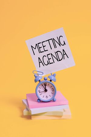 Handwriting text Meeting Agenda. Conceptual photo items that participants hope to accomplish at a meeting Metal alarm clock blank sticky note stacked notepads colored background Фото со стока