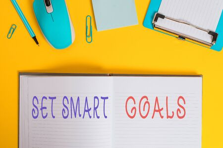 Writing note showing Set Smart Goals. Business concept for giving criteria to guide in the setting of objectives Clipboard sheet striped notepad mouse pencil note colored background