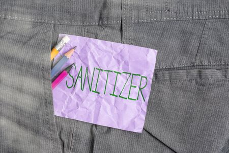 Conceptual hand writing showing Sanitizer. Concept meaning liquid or gel generally used to decrease infectious agents Writing equipment and purple note paper inside pocket of trousers