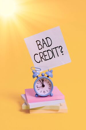 Handwriting text Bad Creditquestion. Conceptual photo inabilityof an individual to repay a debt on time and in full Metal alarm clock blank sticky note stacked notepads colored background