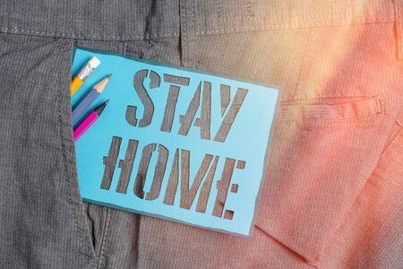 Conceptual hand writing showing Stay Home. Concept meaning not go out for an activity and stay inside the house or home Writing equipment and blue note paper in pocket of trousers