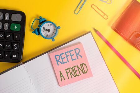 Text sign showing Refer A Friend. Business photo showcasing direct someone to another or send him something like gift Notebook wallet calculator clips pencil note alarm clock color background