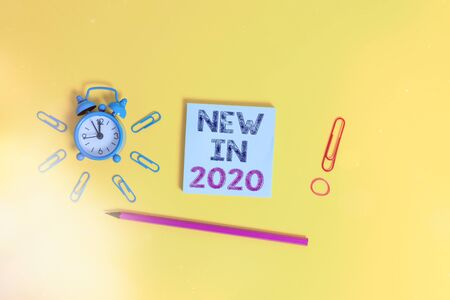Writing note showing New In 2020. Business concept for what will be expecting or new creation for the year 2020 Alarm clock wakeup clips rubber band pencil notepad colored background 版權商用圖片