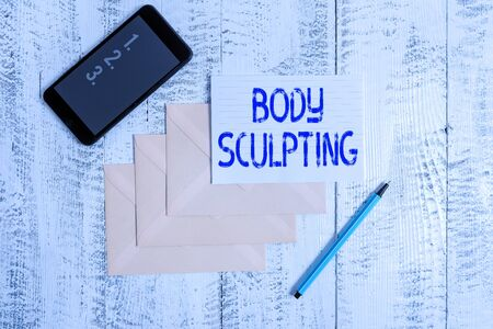 Conceptual hand writing showing Body Sculpting. Concept meaning activity of increasing the body s is visible muscle tone Envelopes marker ruled paper smartphone wooden background
