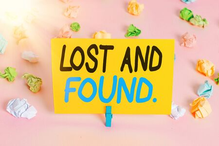 Text sign showing Lost And Found. Business photo text a place where lost items are stored until they reclaimed Colored crumpled papers empty reminder pink floor background clothespin