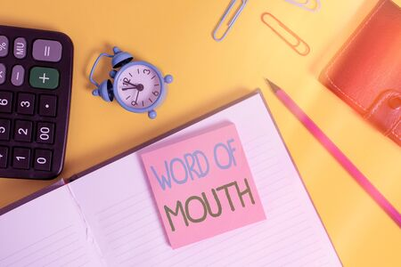 Text sign showing Word Of Mouth. Business photo showcasing information that is transmitted without being written down Notebook wallet calculator clips pencil note alarm clock color background