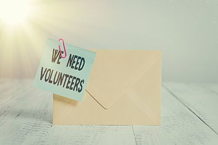 Text sign showing We Need Volunteers. Business photo text someone who does work without being paid for it Standing rectangular colored envelope sticky note clip wooden background